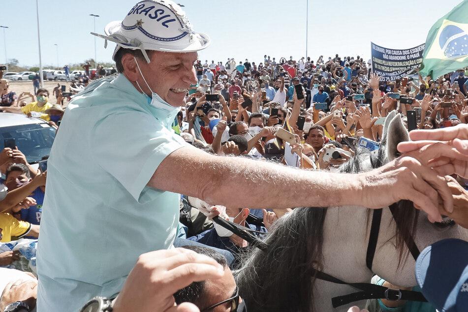 Brasilien, Sao Raimundo Nonato:Präsident Jair Bolsonaro reitet durch eine Menschenmenge und schüttelt mit runtergezogenem Mundschutz Anhängern die Hand.
