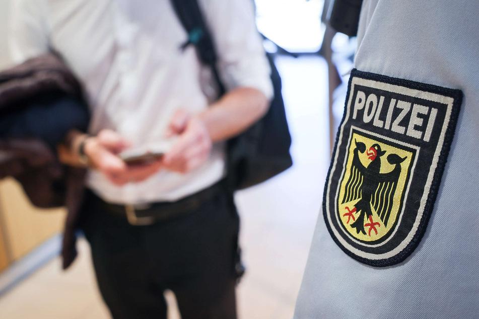 Ein Beamter der Bundespolizei kontrolliert einen Mann. Eine fehlende Maske ist einem gesuchten 28-Jährigen am Bahnhof Harburg zum Verhängnis geworden. (Symbolfoto)