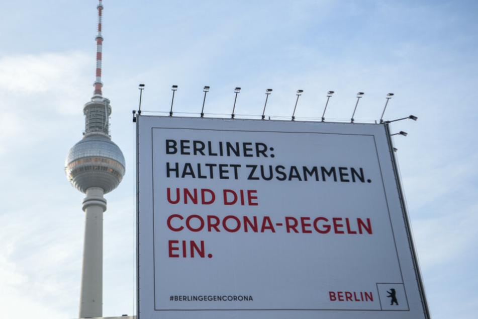 """Vor dem Berliner Fernsehturm steht ein Plakat mit der Aufschrift """"Berliner: Haltet zusammen. Und die Corona-Regeln ein."""""""