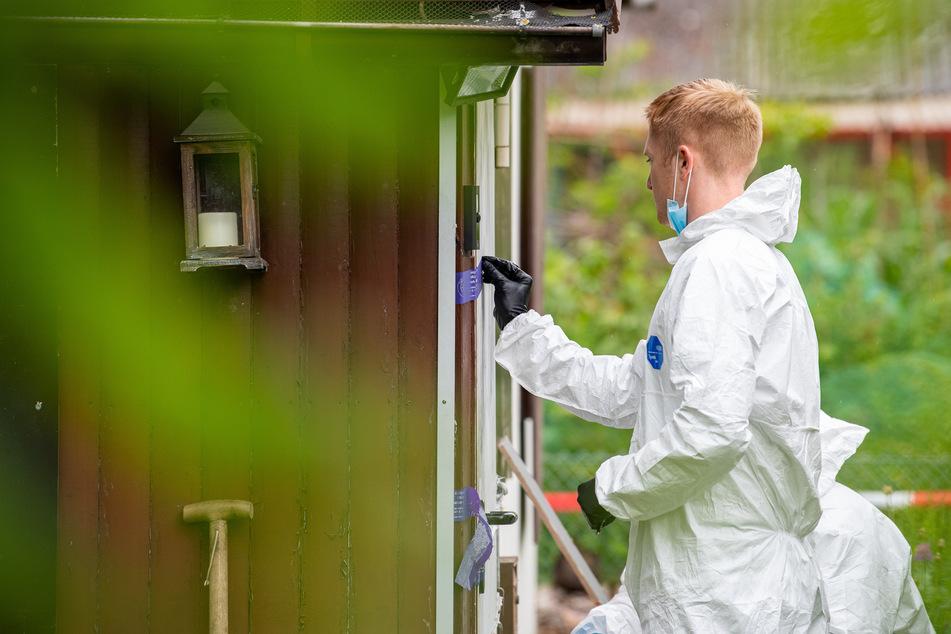 Ein Polizeibeamter der Spurensicherung steht in der Kleingartenkolonie vor der Laube des vermutlichen Haupttäters und öffnet das Polizeisiegel an der Tür.