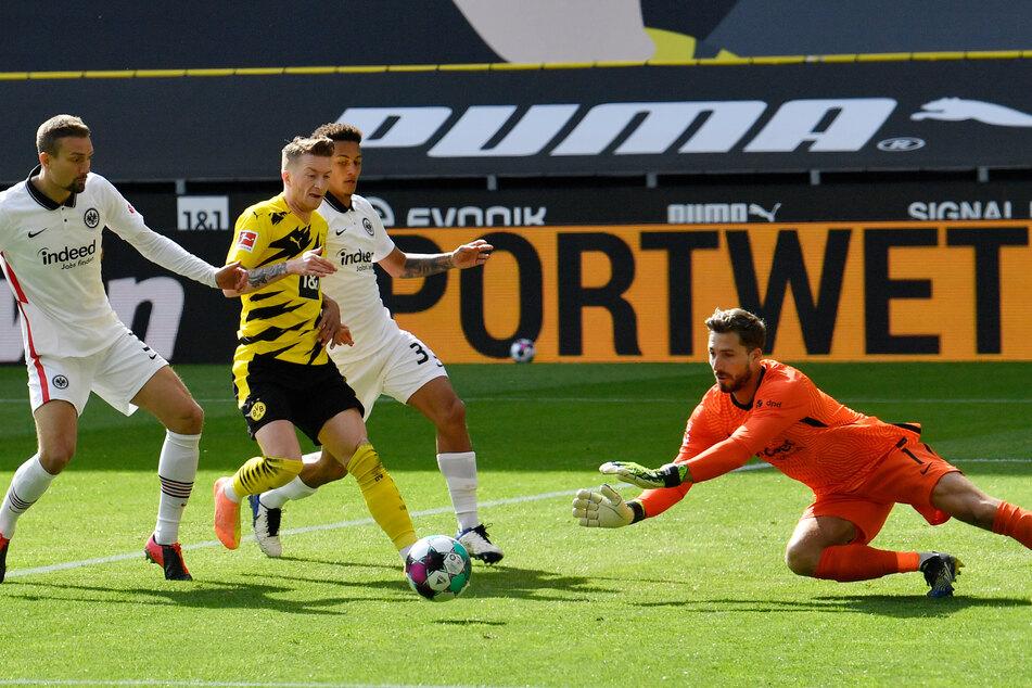 Eintracht Frankfurts Torhüter Kevin Trapp (r.) schnappt sich den Ball vor Borussia Dortmunds Kapitän Marco Reus (2.v.l.).