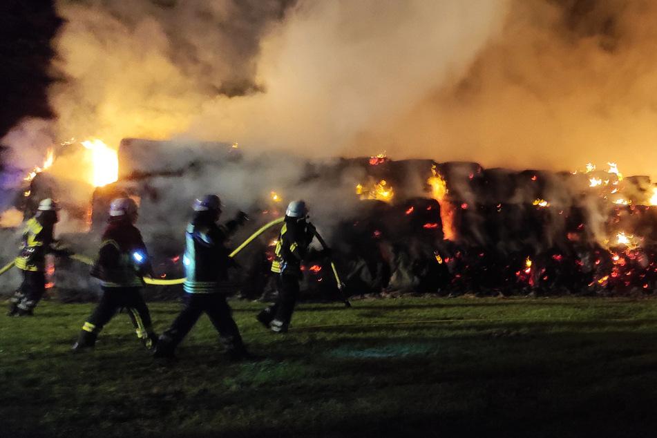 Dichter Rauch macht sich auf dem Feld breit, während Feuerwehrleute gegen die Flammen kämpfen.