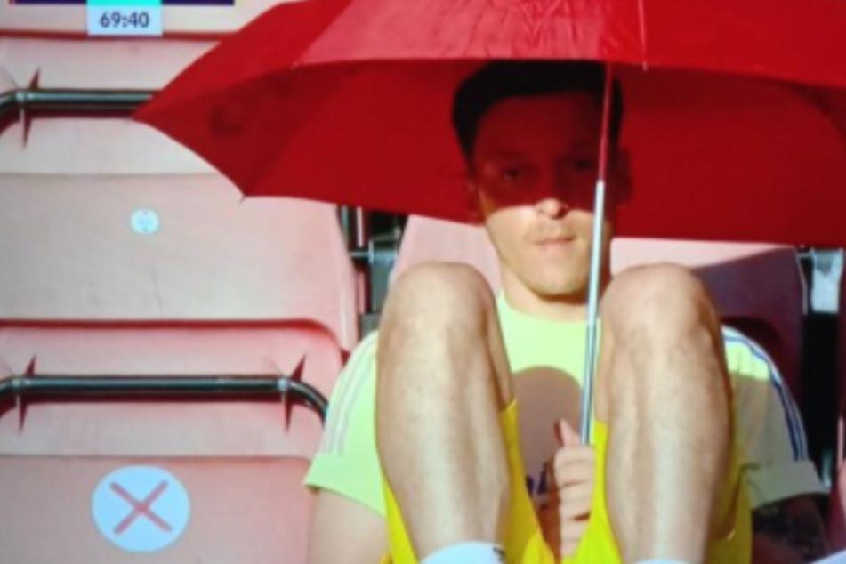 Spott und Häme im Netz: Bankdrücker Mesut Özil mit Sonnenschirm auf der Tribüne