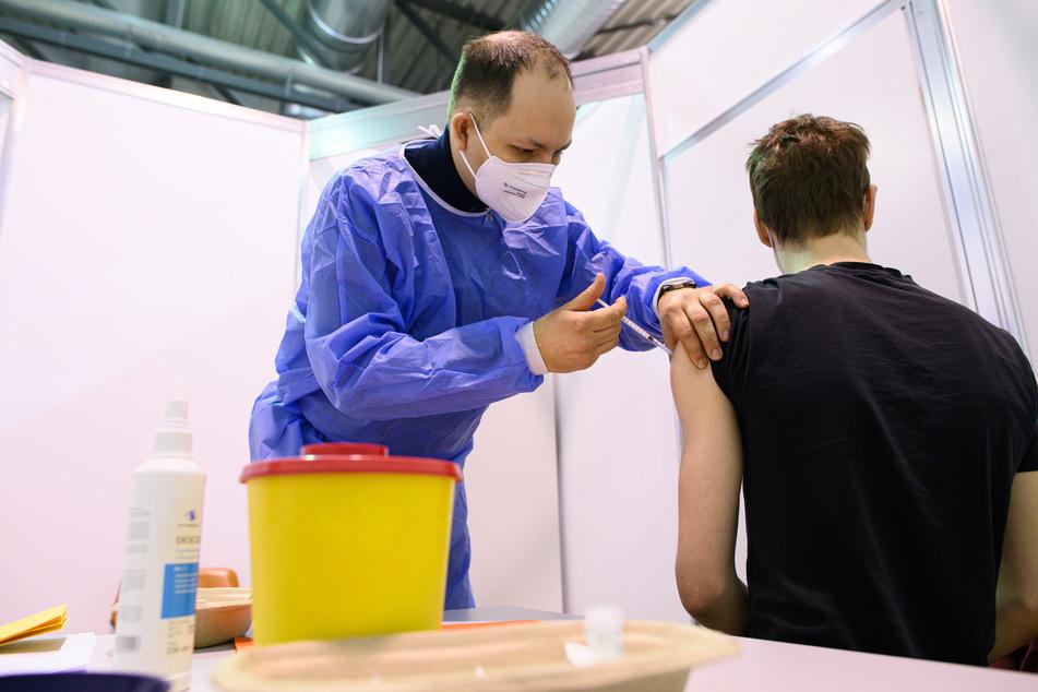 Ein Arzt impft im Impfzentrum in der Messe Dresden einen jungen Mann mit dem Astrazeneca-Wirkstoff gegen Corona.