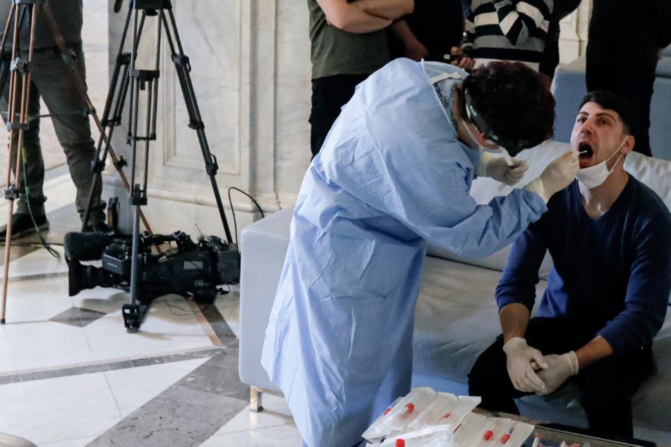 Ein Mitarbeiter im Schutzanzug nimmt in Bukarest für einen Coronavirus-Test Speichelproben von einem Journalisten.