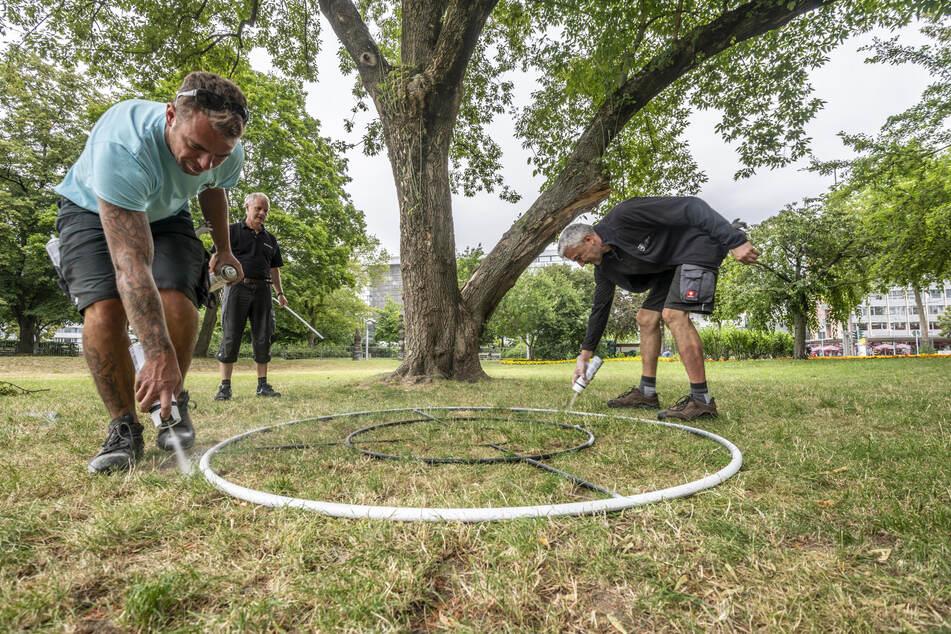 Mitarbeiter der Stadthalle sprühen einen der Kreise auf, mit deren Hilfe der Abstand zwischen den Leuten gewährleistet wird.