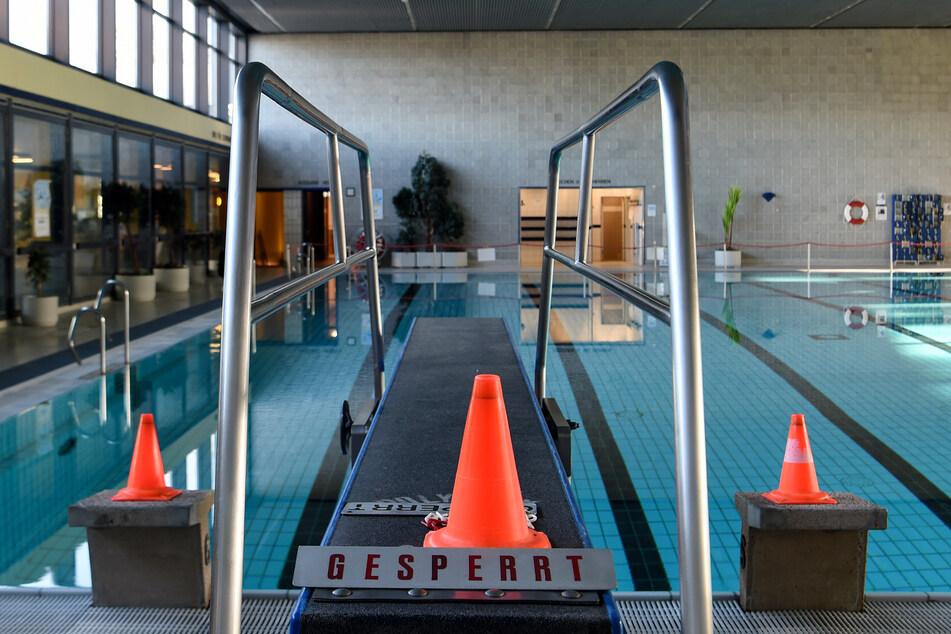"""Ein Sprungbrett mit Warnkegeln und einem Schild mit der Aufschrift """"Gesperrt"""" vor dem leeren Becken im Stadtbad Lankwitz. Die Schwimmbäder sind für den November aufgrund des Lockdowns geschlossen."""