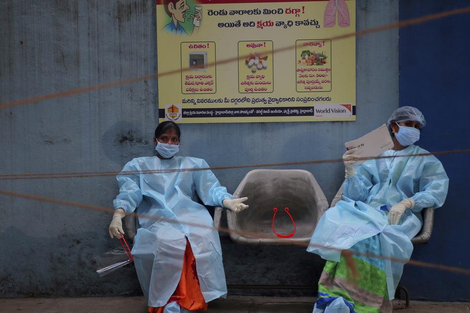 Medizinische Mitarbeiterinnen in Schutzausrüstung ruhen sich vor der Entnahme von Speichelproben für Covid-19-Tests aus.