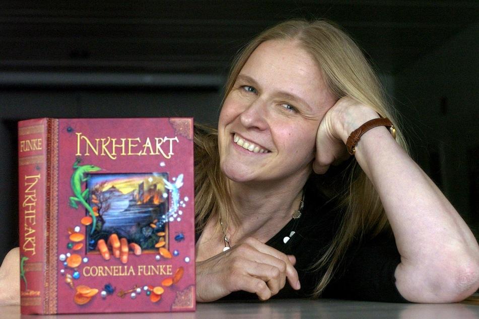 """Cornelia Funke mit der englischen Ausgabe ihres Buches """"Tintenherz""""."""