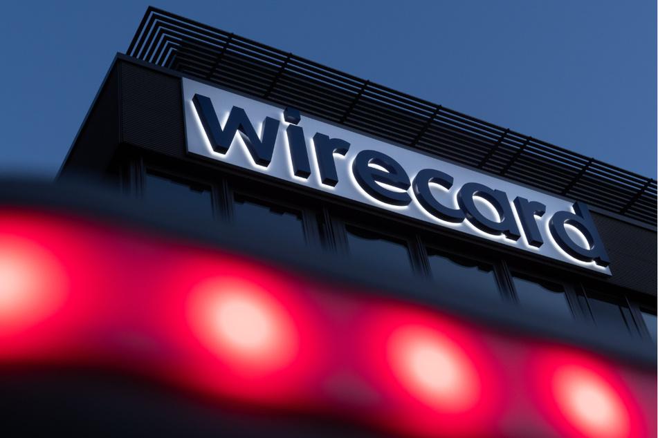 Rote Lichter leuchten vor dem Schriftzug von Wirecard an der damaligen Firmenzentrale des Zahlungsdienstleisters in Aschheim bei München. (Archiv)