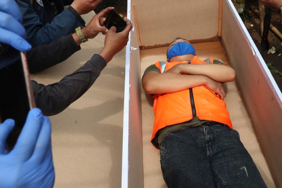 Ein Mann liegt in einem nachgemachten Sarg als Strafe für die Verletzung bestehender Corona-Regeln die der Eindämmung der Pandemie dienen.