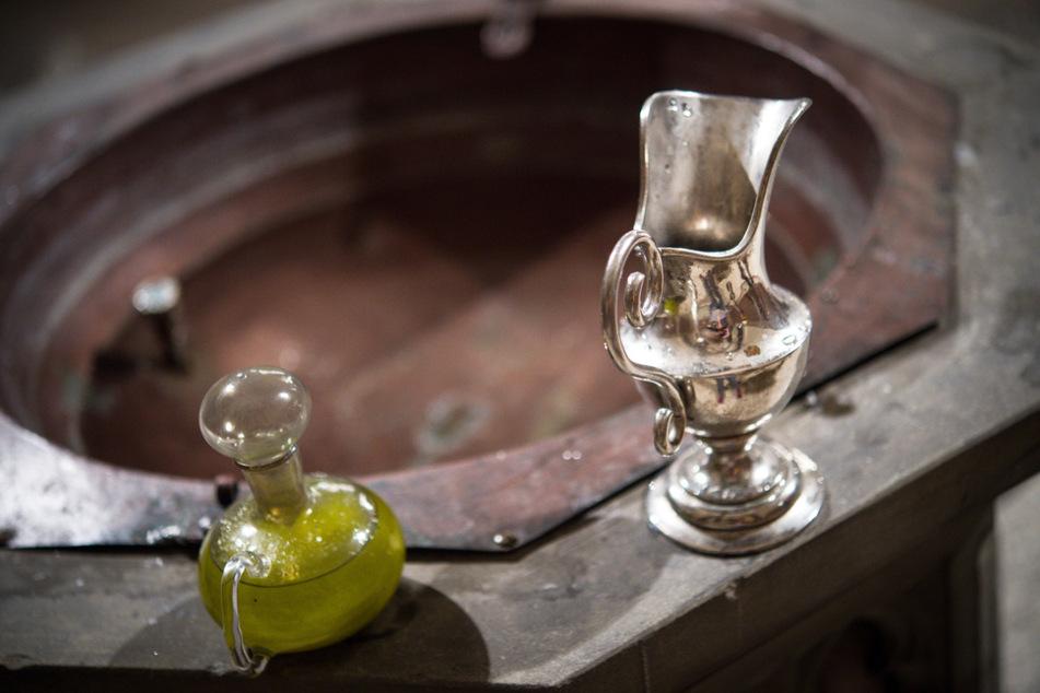 Eine Wasserkaraffe und Chrisamöl in einem Glasflakon stehen in der katholischen Kirche St. Josef in Bamberg am Rande des Taufbeckens für eine Taufe bereit.