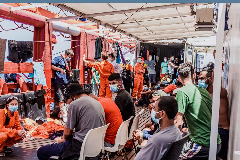 """Migranten und Mitarbeiter von SOS Méditerranée sitzen und stehen an Bord des privaten Rettungsschiffs """"Ocean Viking""""."""