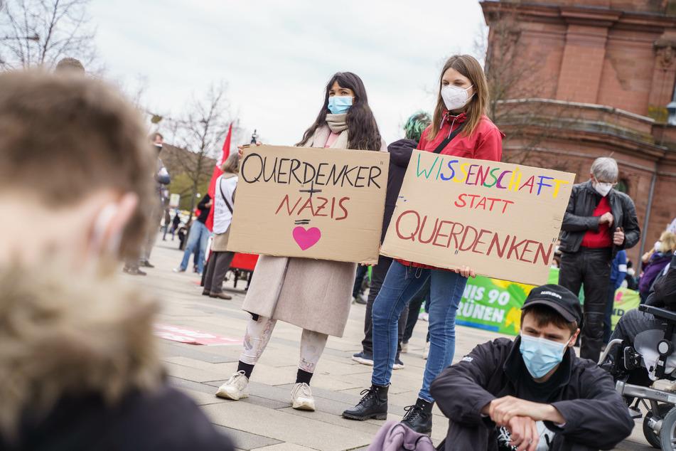 """Zwei Demonstrantinnen gegen eine Kundgebung der """"Querdenken""""-Bewegung halten vor dem Bahnhof Plakate mit der Aufschrift """"Querdenken + Nazis = (Herz)"""" und """"Wissenschaft statt Querdenken""""."""