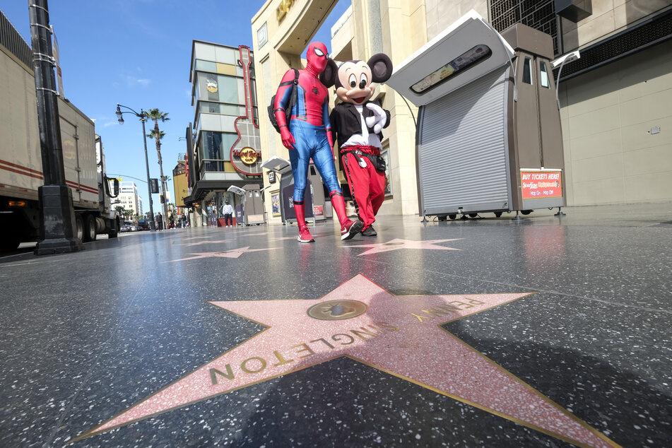 Personen, die als Spiderman und Mickey Maus verkleidet sind, gehen über den Walk of Fame am Hollywood Boulevard in der Nähe des Dolby Theatre.