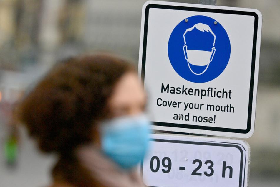 """An einem Schild mit der Aufschrift """"Maskenpflicht - Cover your mouth and nose!"""" in einer Fußgängerzone in der Innenstadt geht eine Frau mit Nase-Mund-Bedeckung vorbei."""
