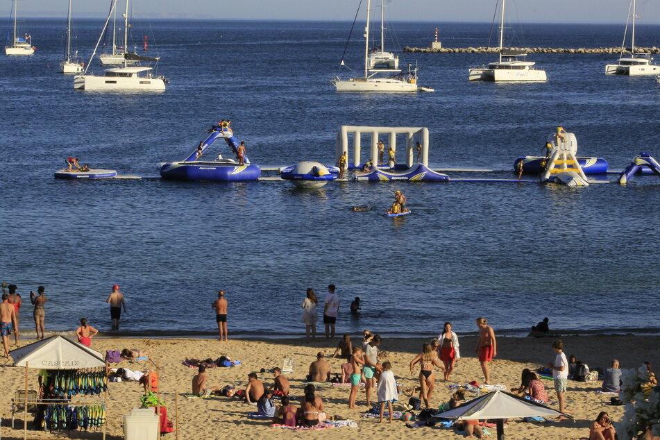 Portugal, Cascais: Badegäste stehen am Strand Conceicao.