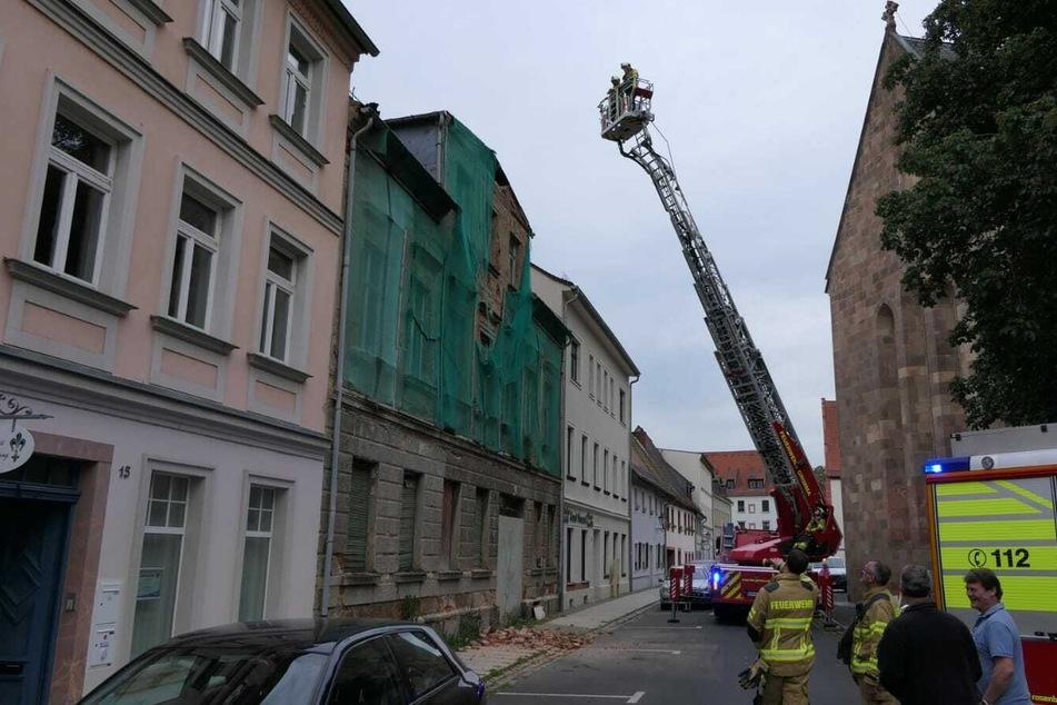 Kameraden der Feuerwehr Grimma sichern das Dach des leerstehenden Hauses.