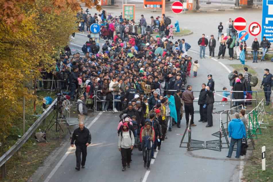 Flüchtlinge überqueren nahe Passau neben einem Polizisten die deutsch-österreichische Grenze. (Archiv)