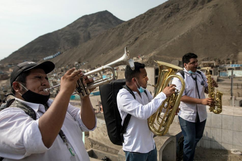 """Lima: Musiker spielen während der Beerdigung eines Mannes, der an Covid-19 gestorben ist, auf dem Friedhof """"Martires 19 de Julio""""."""