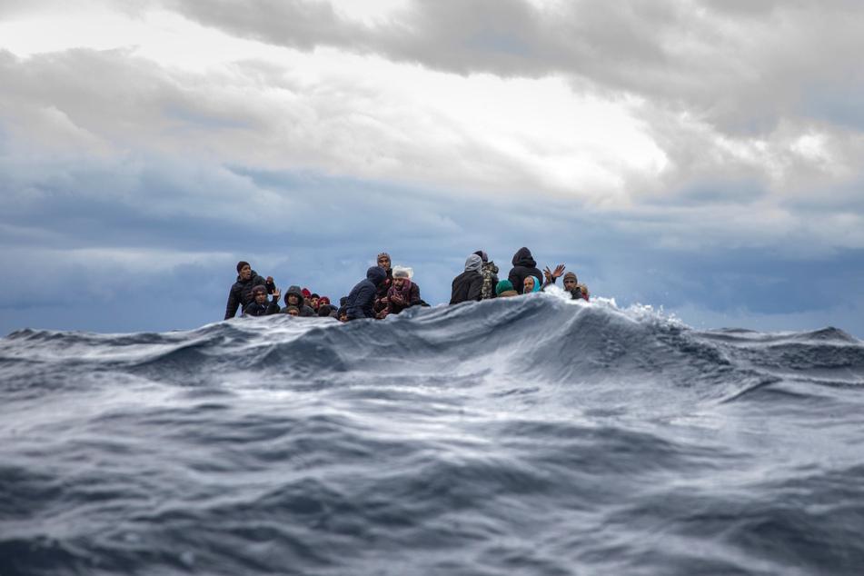 Männer aus Marokko und Bangladesch sitzen in einem überfüllten Holzboot im Mittelmeer vor der Küste von Libyen. (Archivbild)