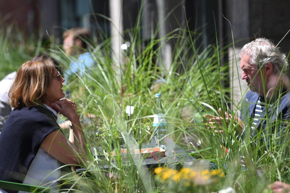 Eine Ehepaar sitzt im Außenbereich eines Restaurants zwischen Blumenkästen mit Gräsern, die als Abstandshalter zwischen den Tischen dienen.