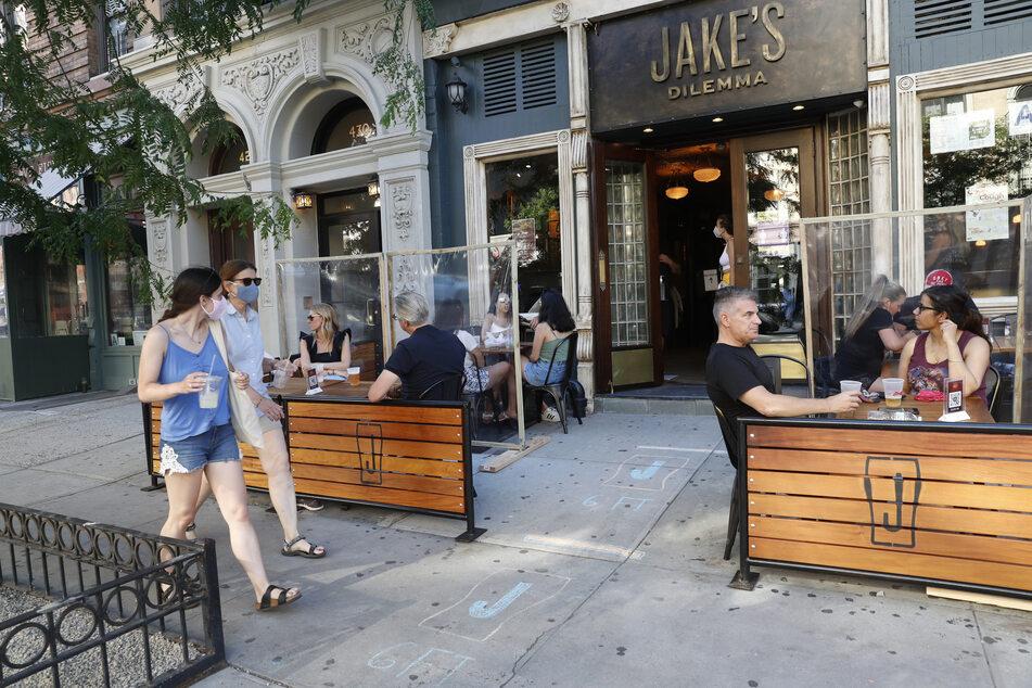 Passanten gehen an einem Restaurant vorbei, an Gästen, die an, mit Schutzwänden, abgetrennten Tischen im Außenbereich sitzen.