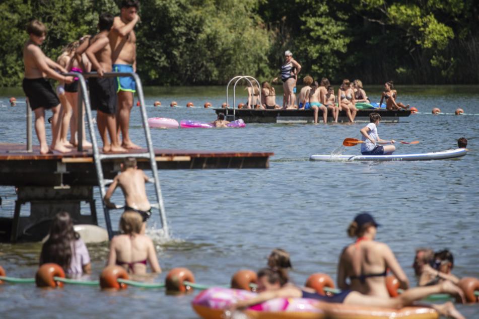 Menschen genießen den sonnigen Tag am Badesee in Plüderhausen.