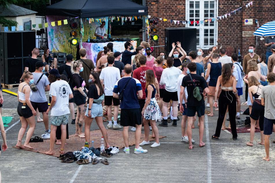Junge Leute tanzen im Hof des Musikzentrums. Sie nehmen an einem Projekt teil, das Erkenntnisse bringen soll, wie sicher Tanzveranstaltungen unter freiem Himmel sind.