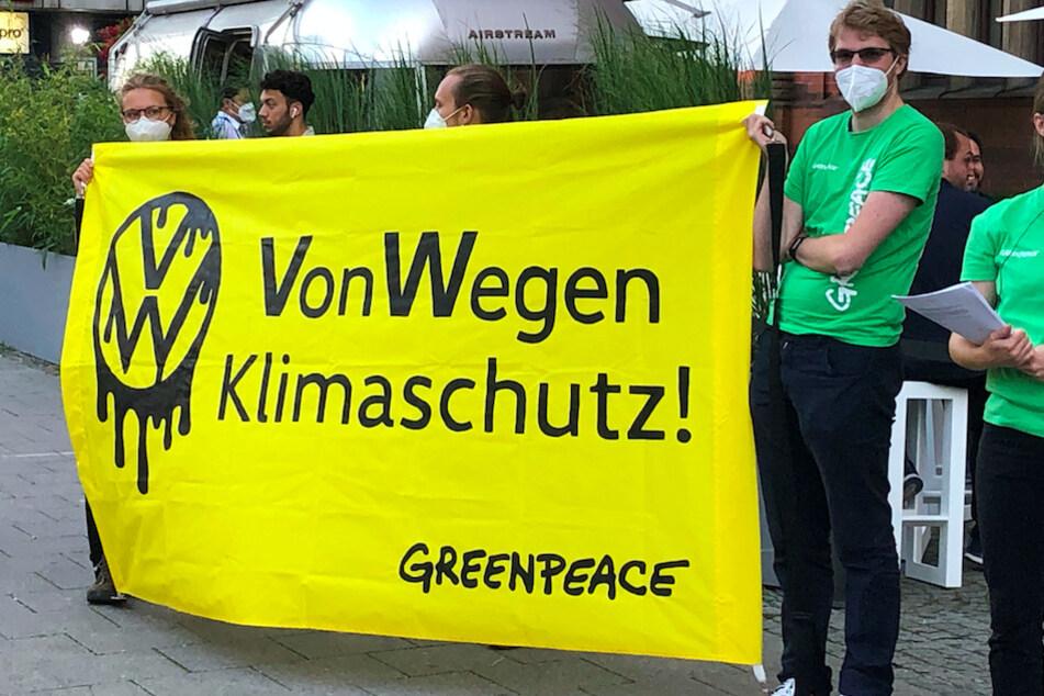 """Demonstranten von Greenpeace stehen mit einem Poster """"VW - Von Wegen Klimaschutz!"""" vor einer Halle, in der eine Veranstaltung von Volkswagen stattfand."""
