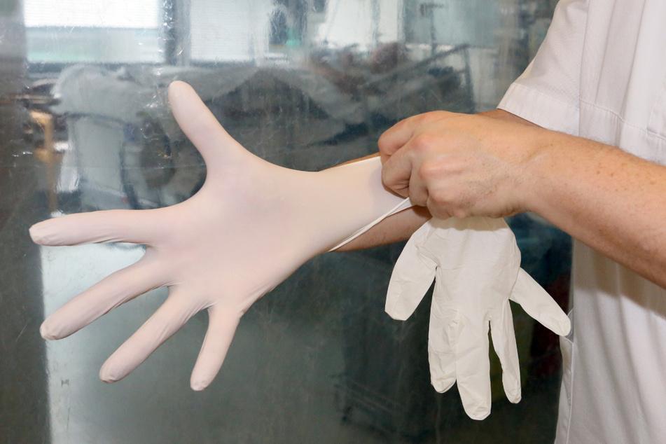 Ein Pfleger auf der Intensivstation in einem Krankenhaus zieht sich Handschuhe an.