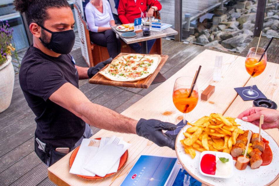 Ein Kellner bringt Gästen mit Maske ihr bestelltes Essen an den Tisch.