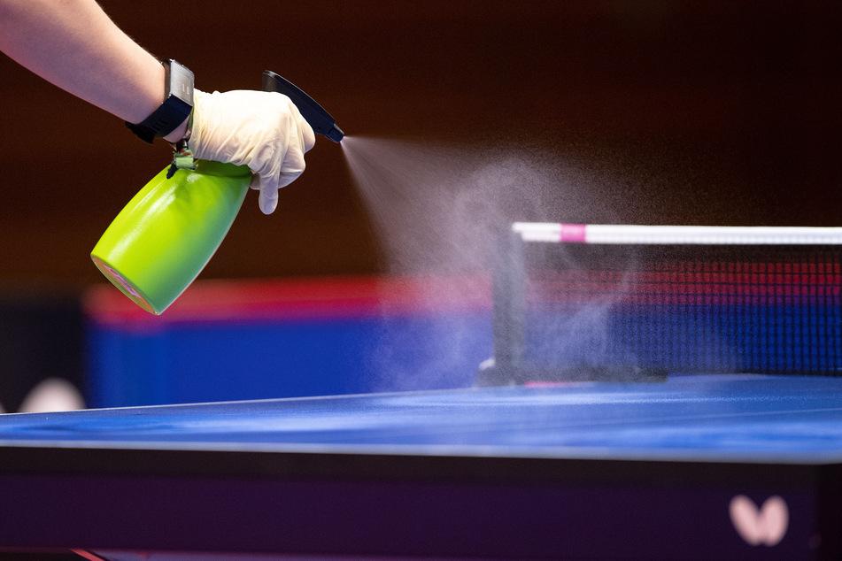 """Ein Helfer desinfiziert nach einer Partie beim """"Düsseldorf Masters"""" Halbfinale die Tischtennisplatte."""