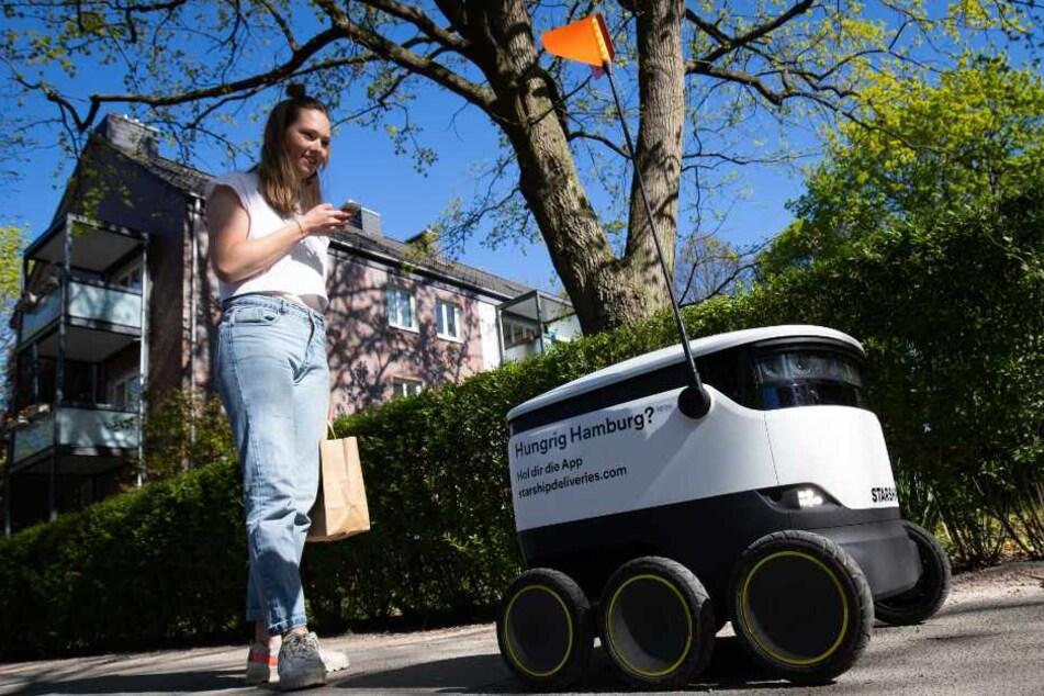 """Kundin Leonie Gehrckens steht mit ihren bestellten Lebensmittel vom Bioladen """"Bio.lose"""" neben einem Lieferroboter."""