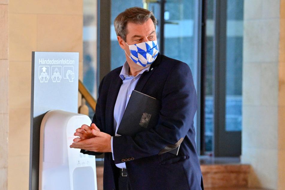 Markus Söder (53, CSU), Ministerpräsident von Bayern, trägt einen Mund-Nasen-Schutz, während er sich Hände an einem Desinfektionsmittel-Spender desinfiziert.