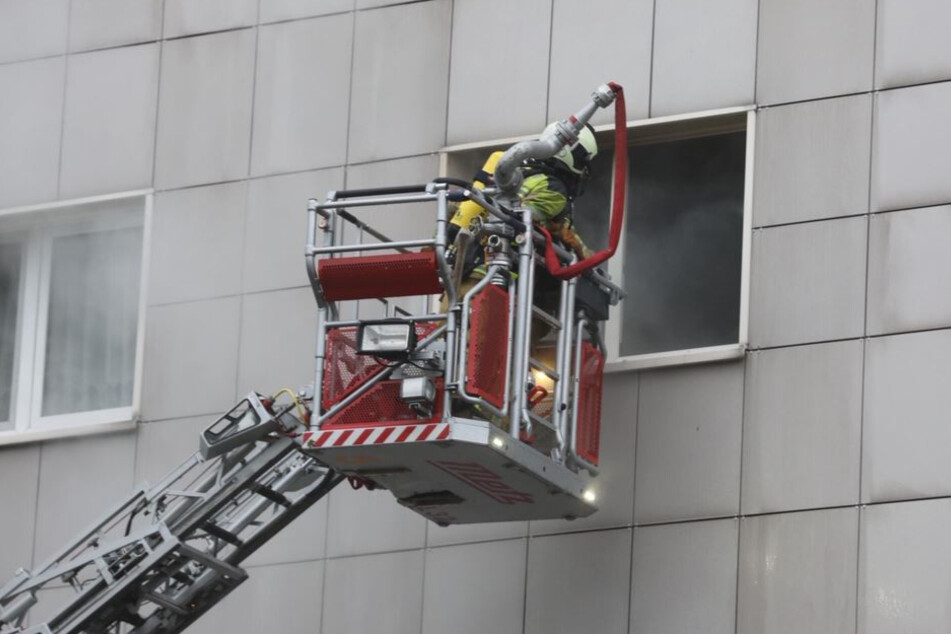 Die Feuerwehr bekämpft den Brand durchs Fenster.