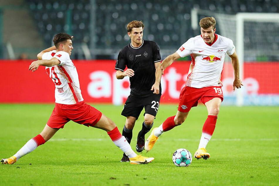 Leipzigs Startelf-Debütant Lazar Samardzic (l.) und Alexander Sörloth (r.) versuchen, Jonas Hofmann zu stoppen.