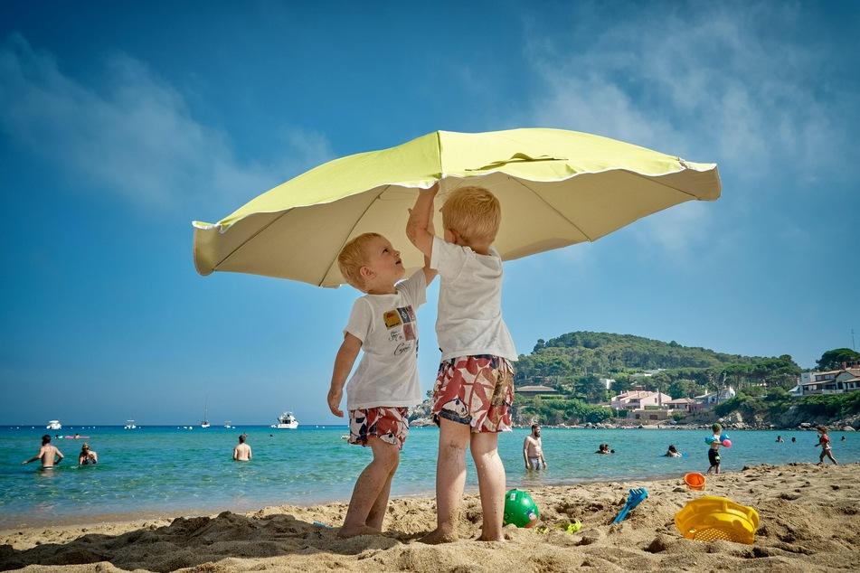 Luftige und längere Kleidung sowie ein schattiges Plätzchen: So sind Kinder in der Sonne wirksam geschützt.