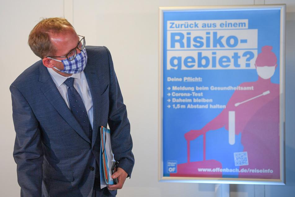 """Kai Klose (Bündnis 90/Die Grünen), Sozialminister des Landes Hessen, steht zu Beginn einer Pressekonferenz im Offenbacher Stadion neben einem Plakat mit der Aufschrift """"Zurück aus einem Risikogebiet?"""""""
