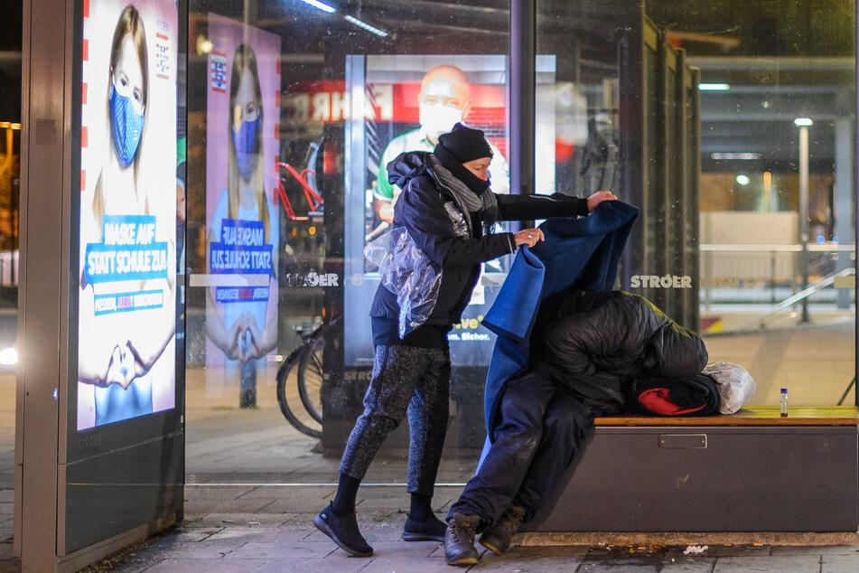 Elfie Ilgmann-Weiß, Sozialarbeiterin, legt einem Obdachlosen, der in einer Bushaltestelle schläft, eine Decke über.