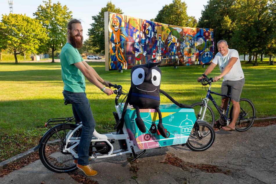Die Mobitag-Organisatoren Bjarne Lotze (27, l.) und Marc Stoll (41) fahren mit Mobilitätswoche-Maskottchen Edgar Rad im Sportforum.