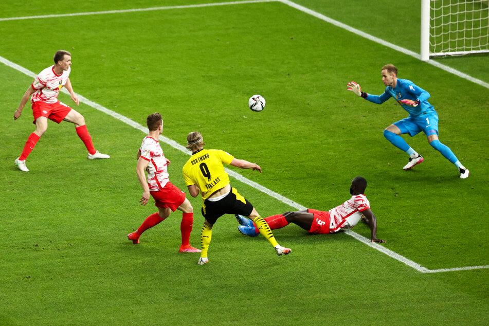 Erling Haaland (M.) lässt Dayot Upamecano (2.v.r.) aussteigen und schlenzt die Kugel an RB-Keeper Peter Gulacsi vorbei zum 2:0 für Borussia Dortmund ins linke Eck.