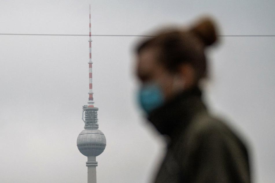 Eine Fußgängerin läuft mit Mundschutz am Berliner Fernsehturm vorbei.