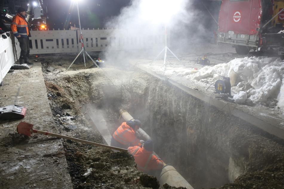 Mitarbeiter der Stadtwerke reparieren die Fernwärmeleitung.