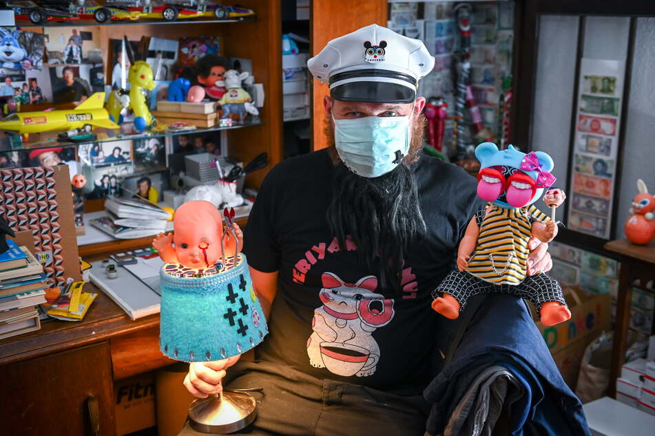 """Hinter Mütze und Maske verbirgt sich der Künstler """"Milchmann"""" - in den Händen skurrile Puppenlampen."""