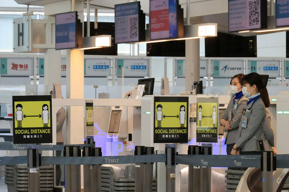 Signs to require social distancing are displayed at the empty international terminal of the Haneda airport in Tokyo, Japan.