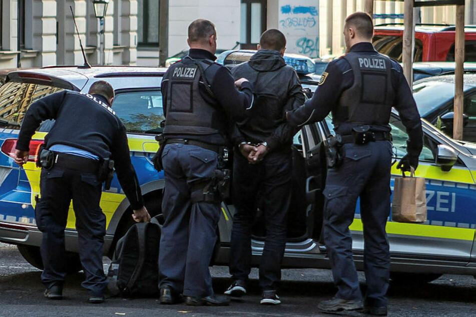 Polizisten führen den festgenommenen Einbrecher zum Streifenwagen. Am Freitag muss er zum Haftrichter.