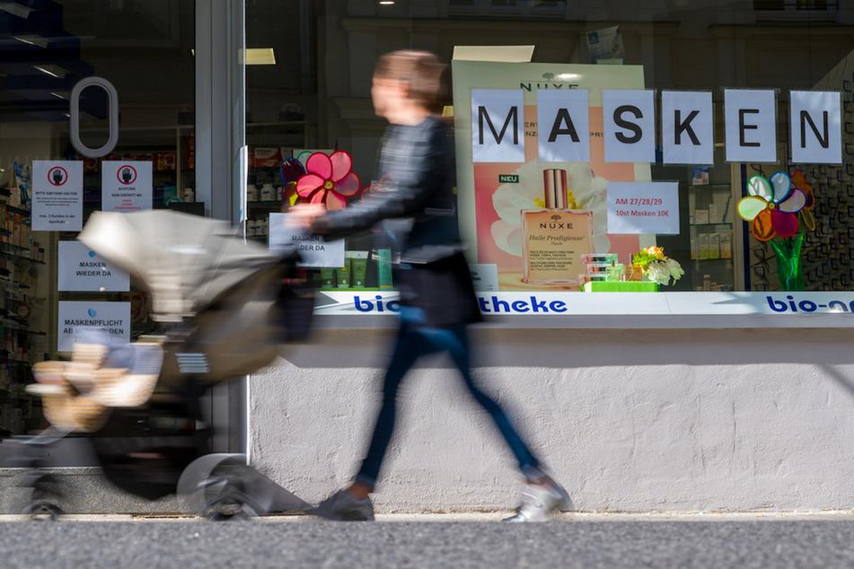 Eine Frau schiebt einen Kinderwagen an einer Apotheke vorbei, die Mundschutzmasken anbietet.