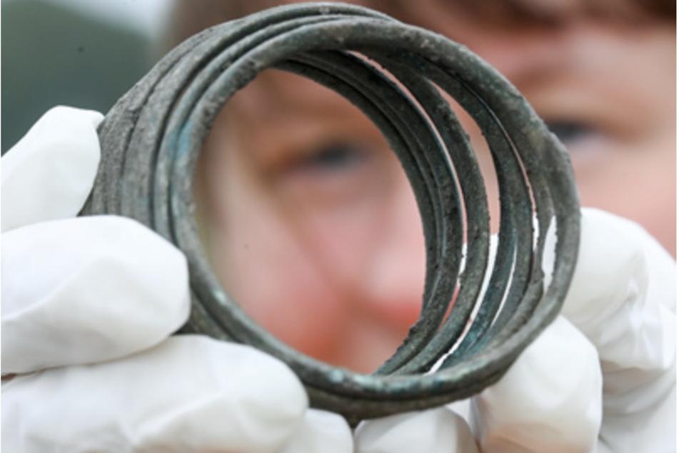 Eine Grabungstechnikerin zeigt eine bronzene Armspirale aus der Zeit der Himmelsscheibe von Nebra in Friedrichsschwerz bei Halle. Der Schmuck lag als Beigabe in einem Grab mit einem Baby.