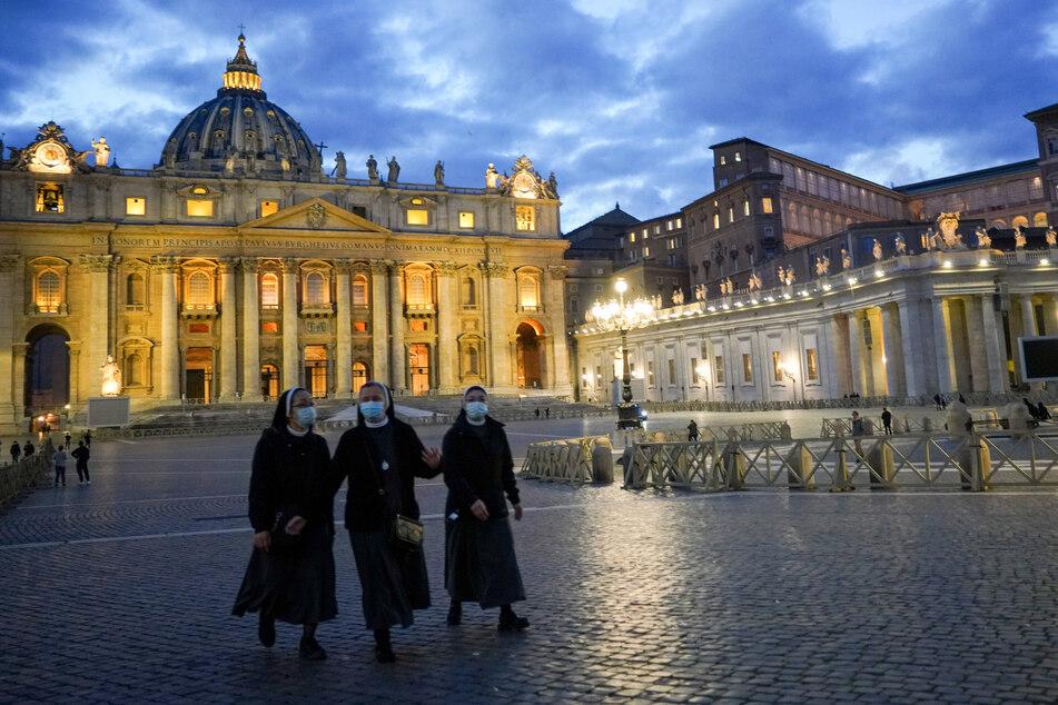 Nonnen mit Mund-Nasen-Bedeckungen gehen über den leeren Petersplatz.